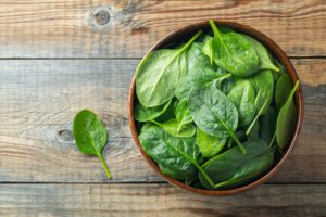 Spinach in a brown bowl on wood surface