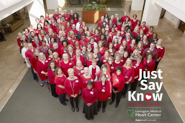 """Just Say Know to heart disease"" flyer of hospital employees in red scrubs standing together to form a heart shape"