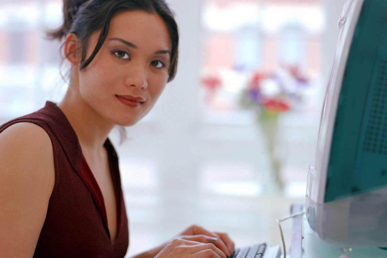 A woman smiling slightly and looking towards the camera while her hands rest on the keyboard of an old Mac desktop computer.