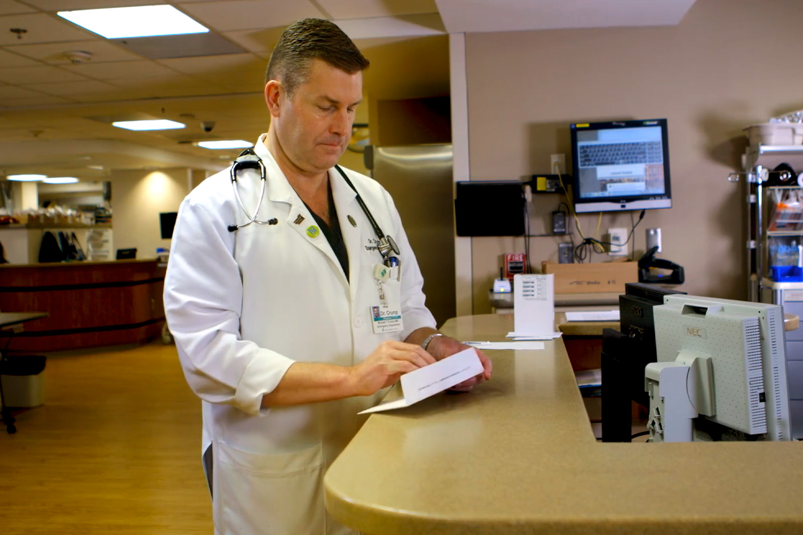 Dr. Todd Crump at work, standing at the clinic desk reading a medical pamphlet.