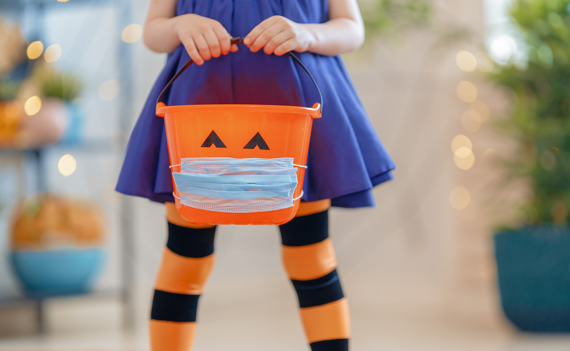 Child with Halloween candy basket wearing mask