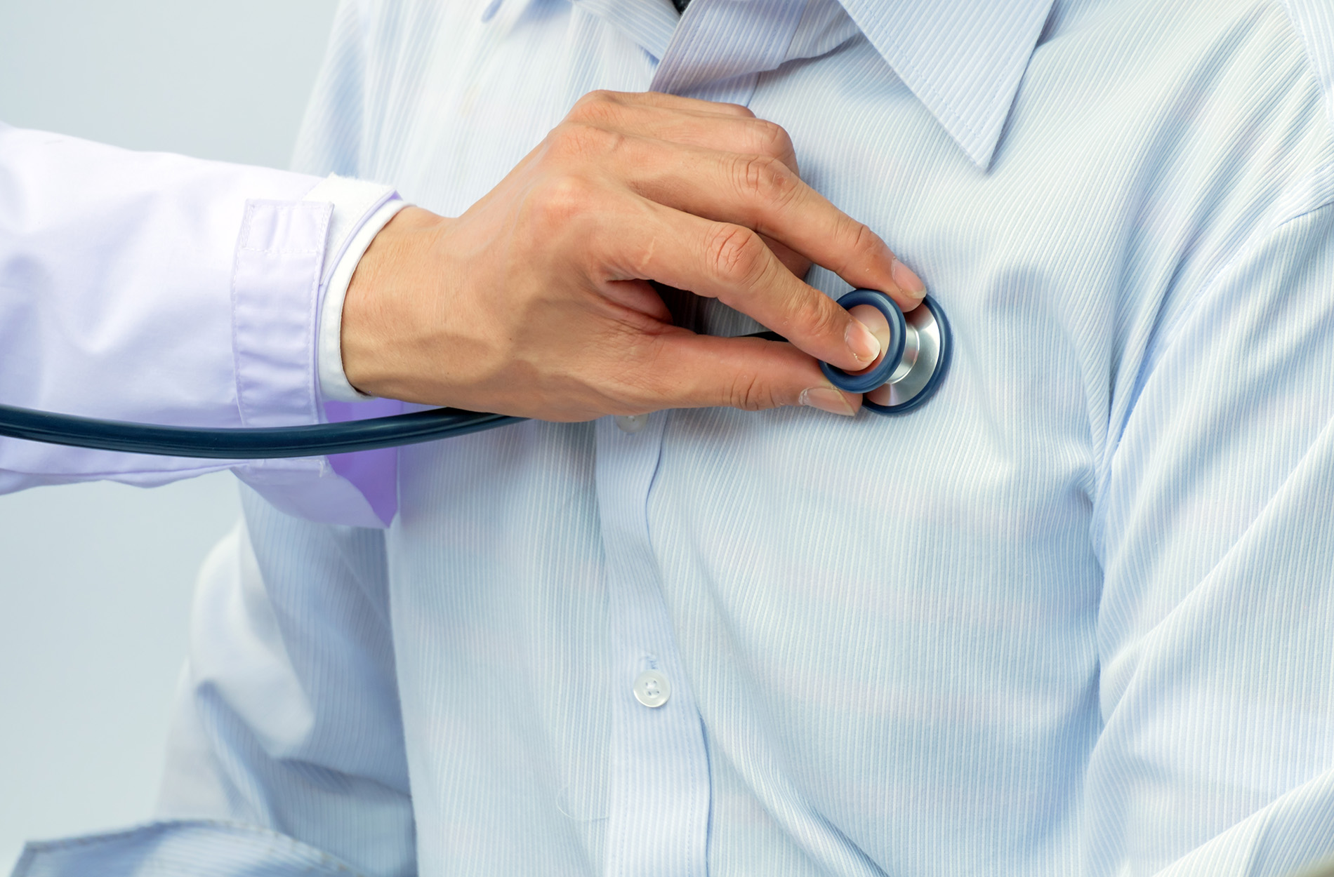 Doctor's hand holding stethoscope on patient's chest