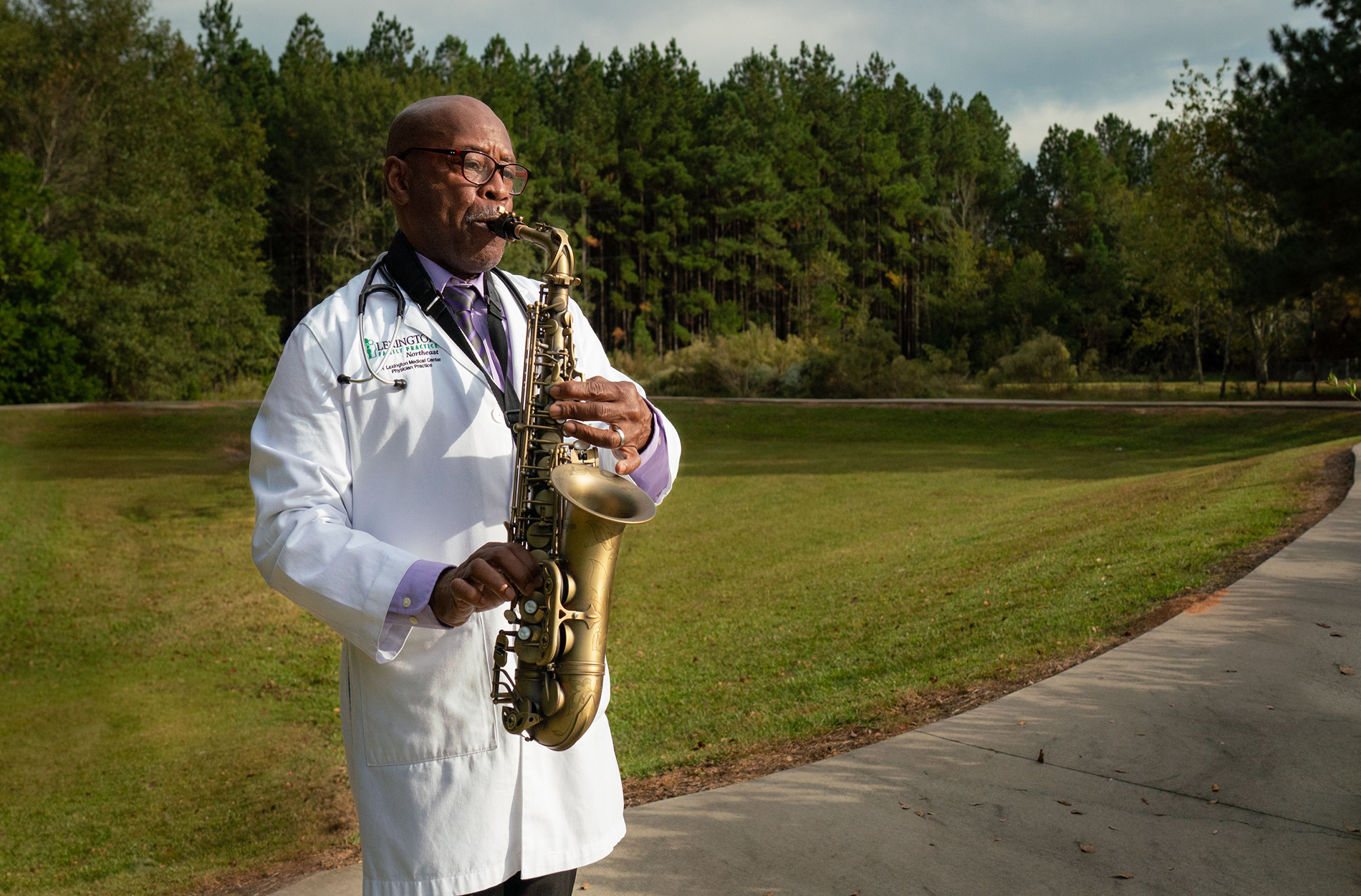 Dr. Marion playing saxophone outside wearing his white lab coat