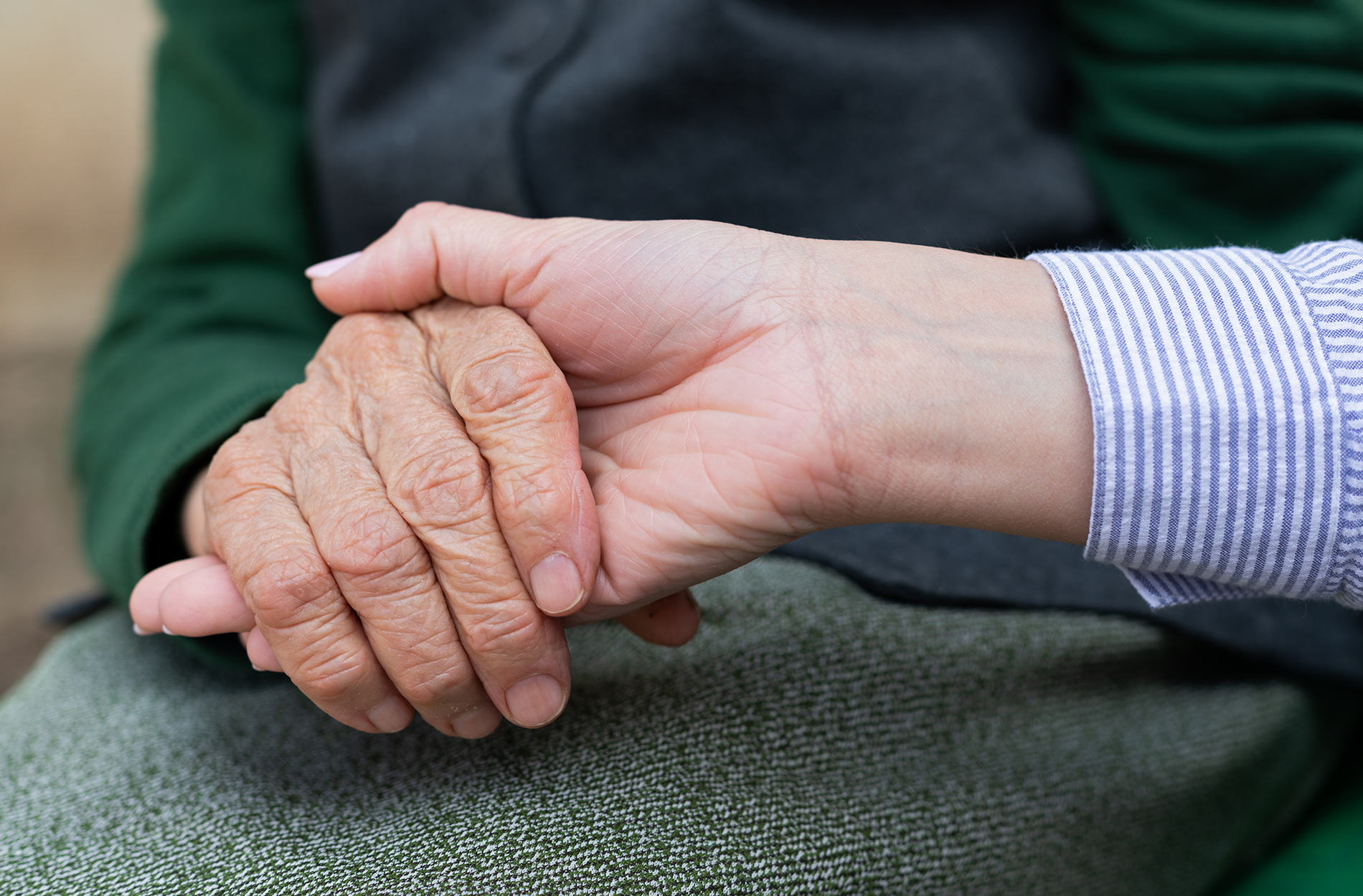Young hand touching elderly hands