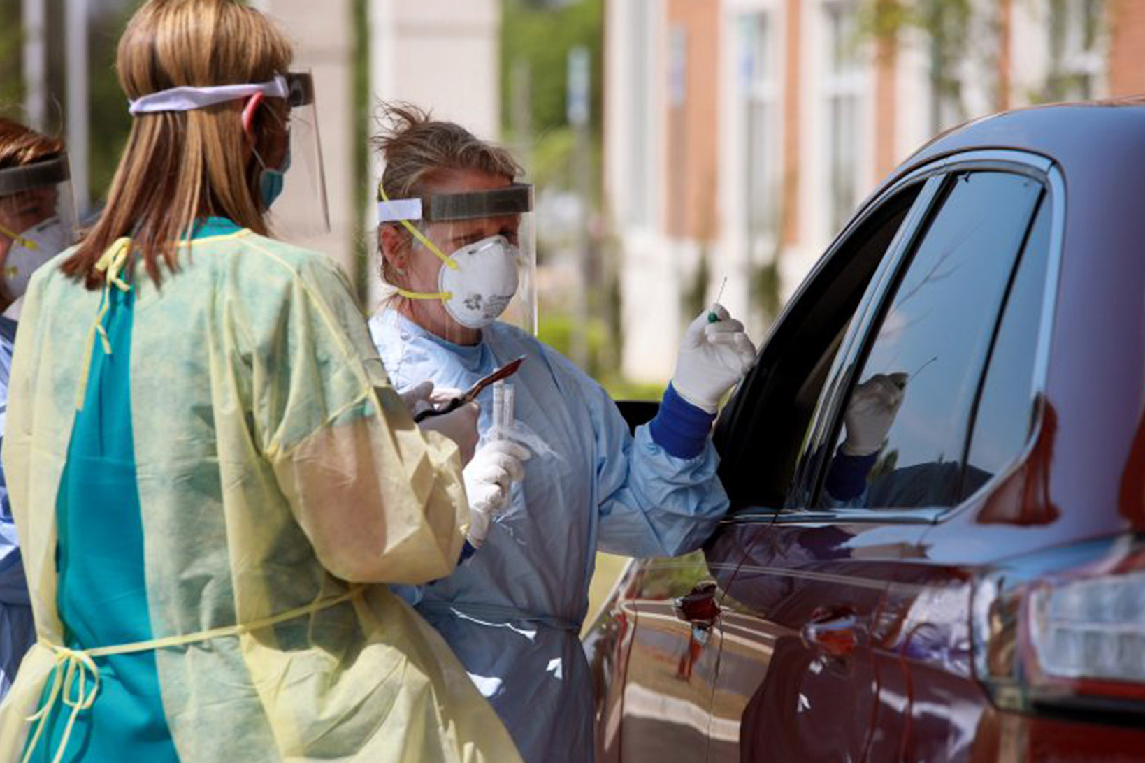 Two health care workers in scrubs, plastic protective gear and masks speak with a person through the driver's window of a vehicle.
