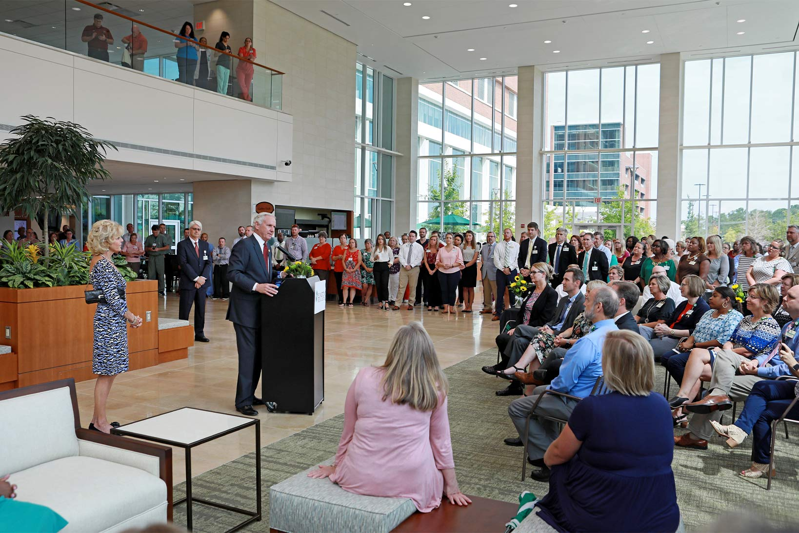 Governor Henry McMaster at a podium giving a speech in the lobby of Lexington Medical Center to an audience.