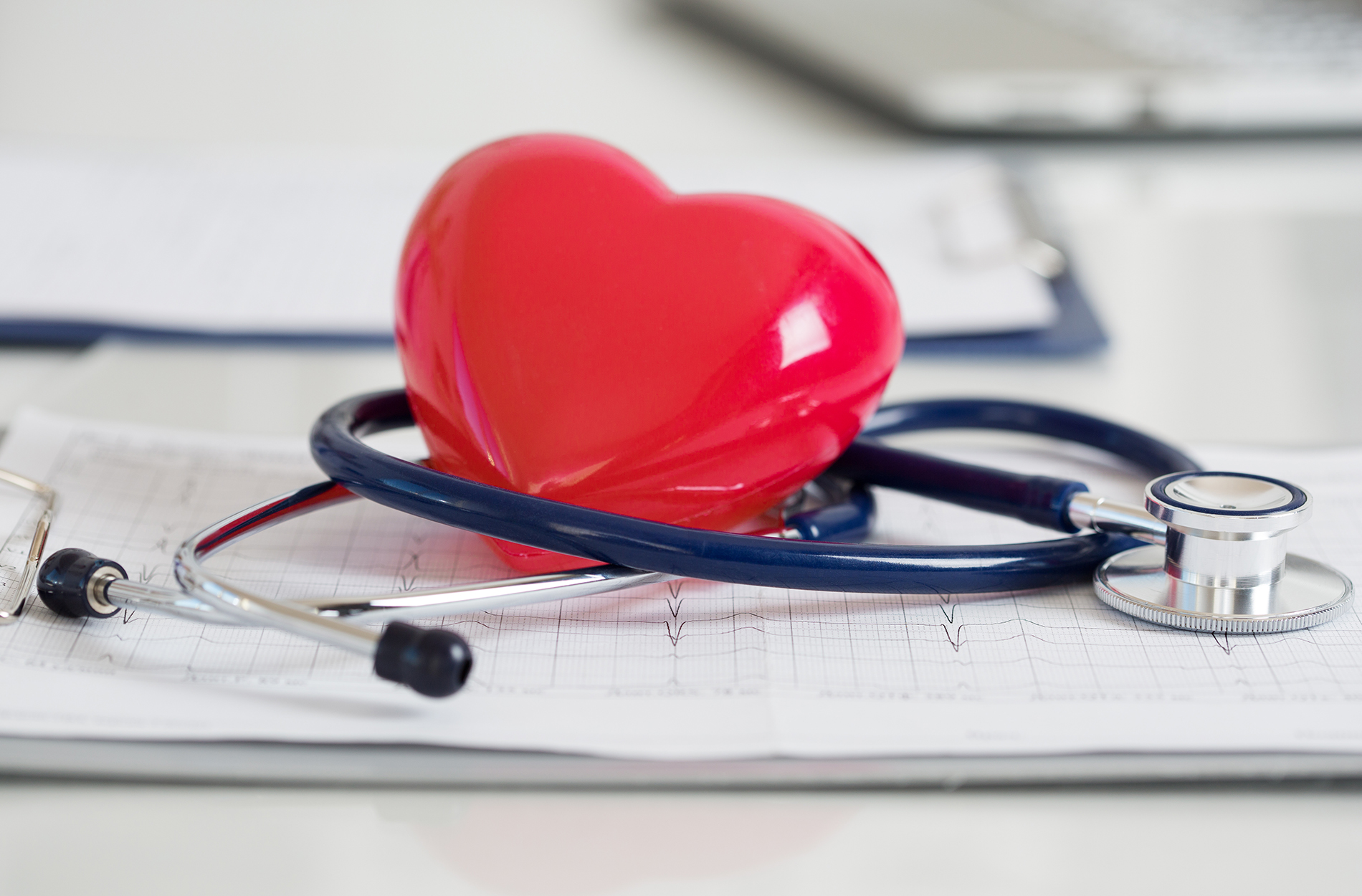 Red heart and stethoscope on physician clipboard