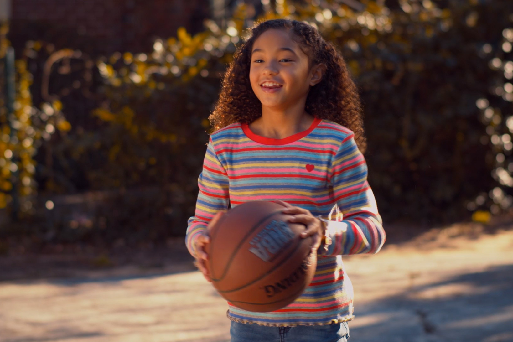 A little girl in a colorful shirt smiling while getting ready to pass a basketball to someone out of view outside on a sunny day.