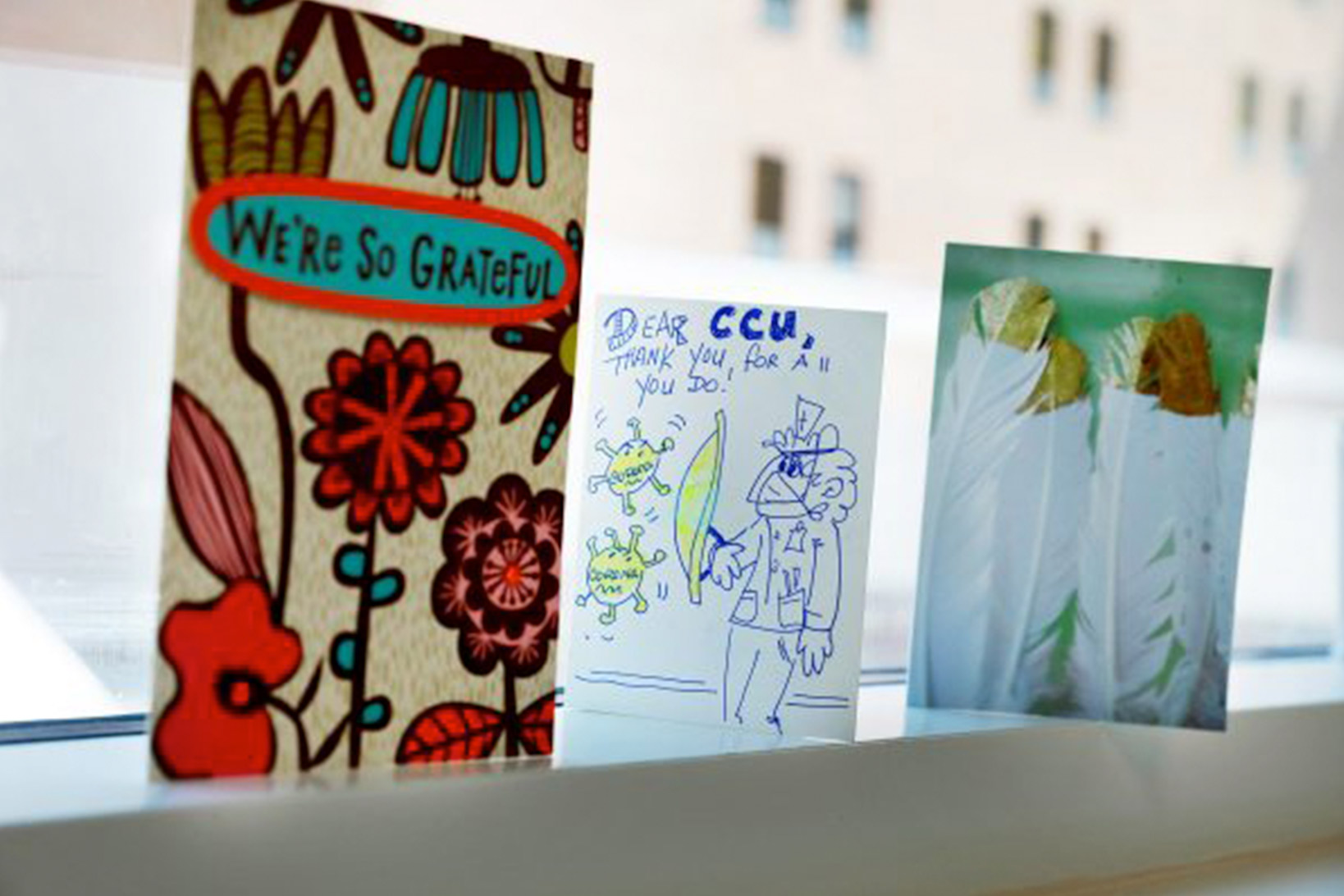 Three hand-made cards wishing patients of coronavirus well, with text We're So Grateful, flower designs, cartoon drawings and feathers on a windowsill.
