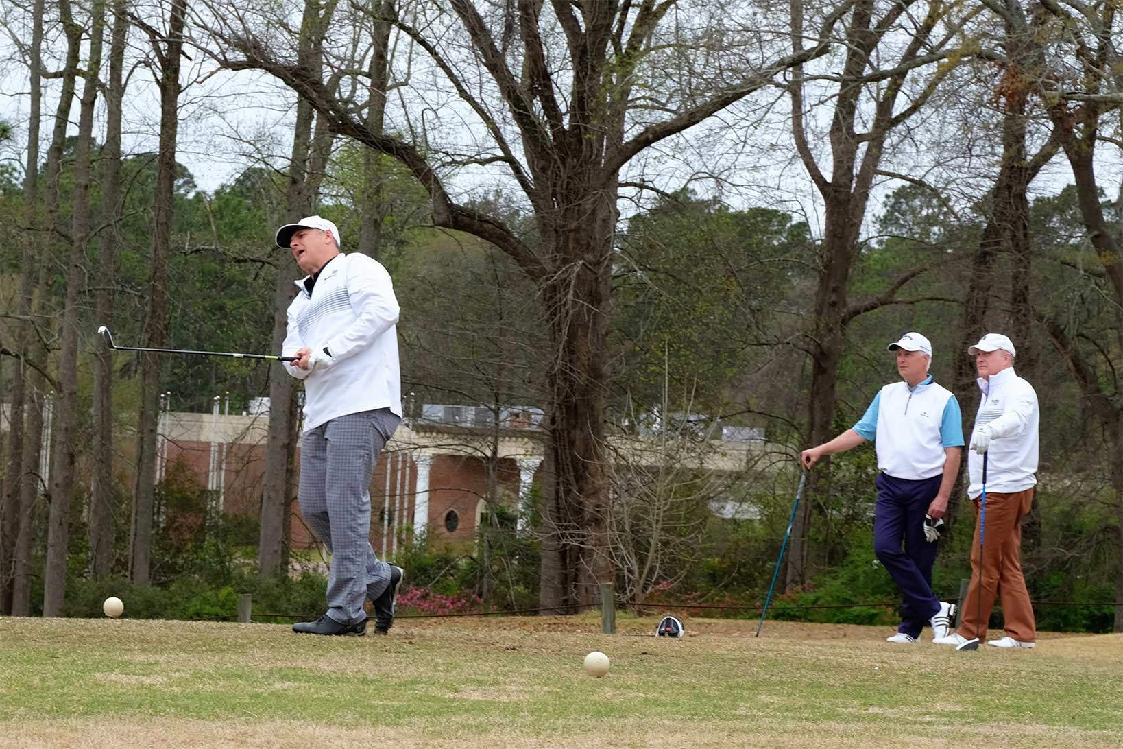 Three men playing golf, with two in the background observing the shot of another man, still in his golf stance, grimacing at his performance.