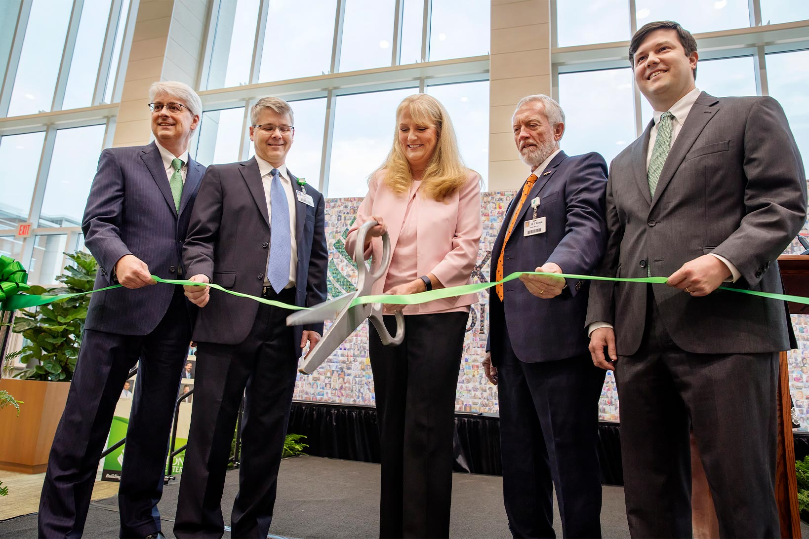 Four people in suits holding a green ribbon and posing for photos while another person in the middle cuts the green ribbon with a large pair of scissors.