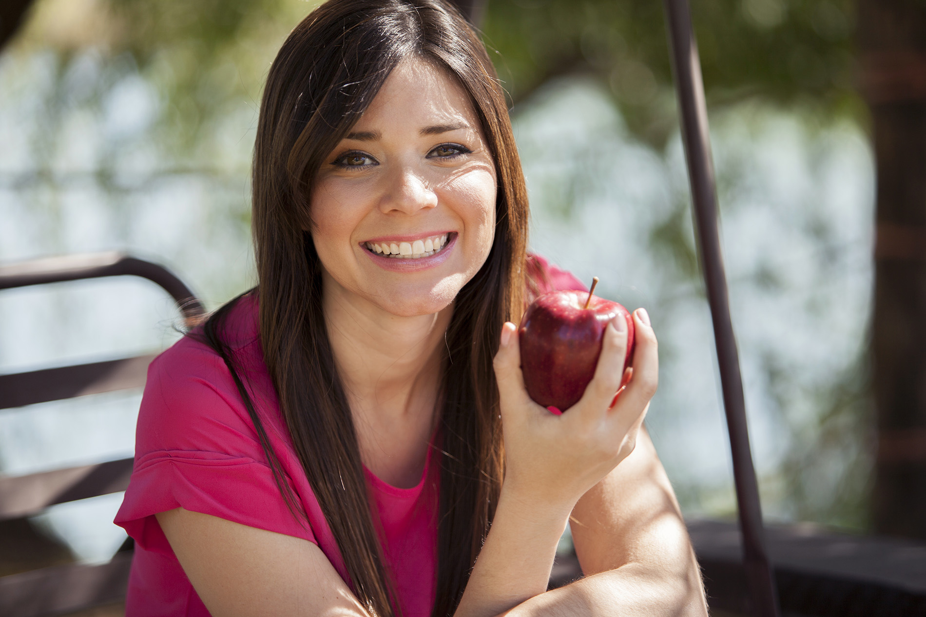Young brunette woman holding red apple