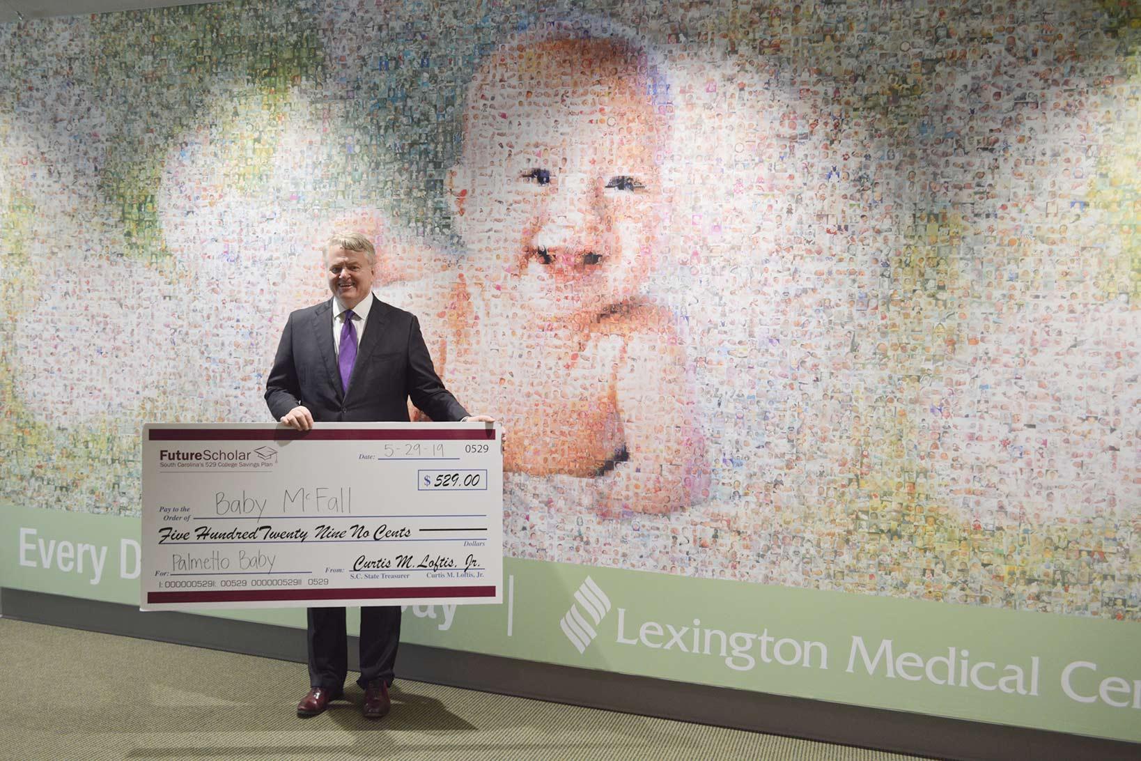 Treasurer Loftis holding a large check addressed to Baby McFall posing in front of the baby mosaic in the new patient care tower.