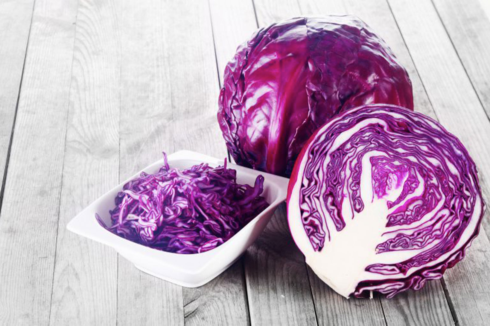 A cross section of a red cabbage leaning against another red cabbage, next to a small white bowl of shredded red cabbage, on wood.
