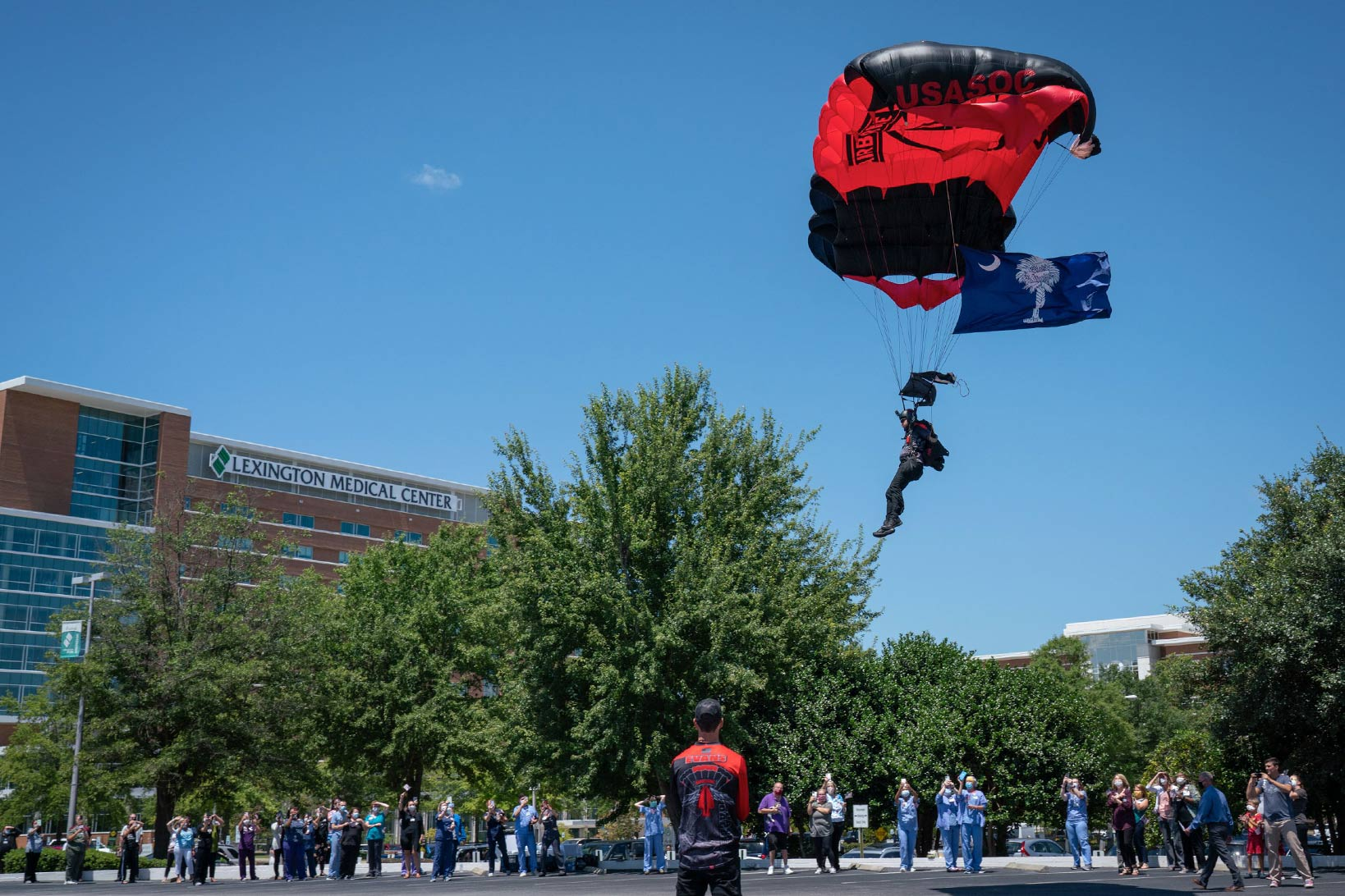 A Black Dagger member parachuting on the Lexington Medical Center main campus, waving the South Carolina flag, as staff and patients watch.