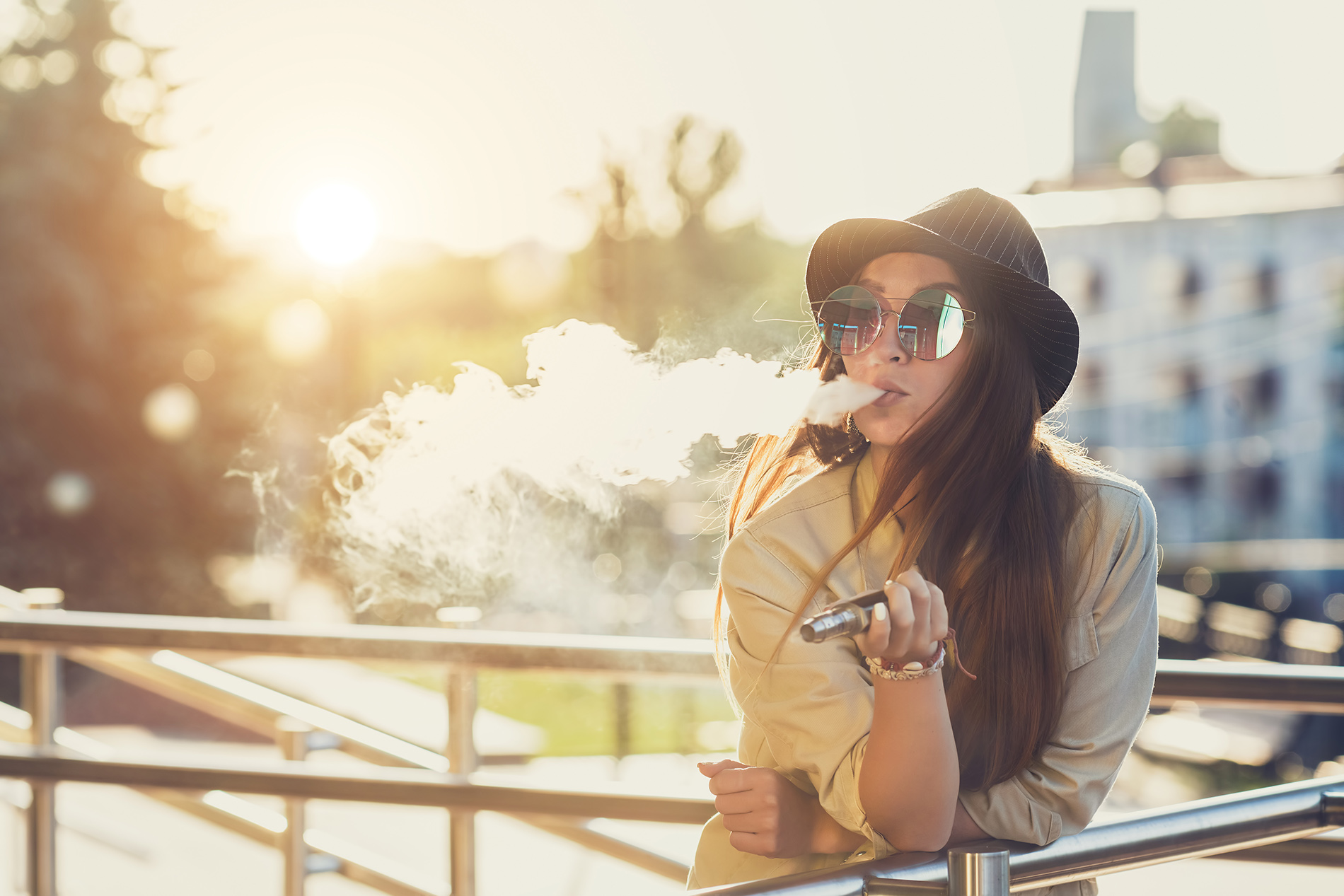 Young woman vaping outside