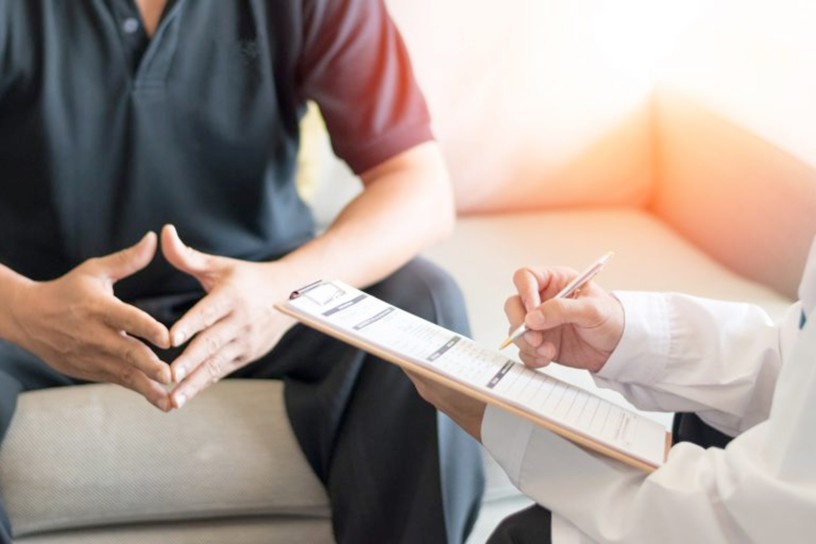 A doctor makes notes on a clipboard while talking to a patient, whose hands are steepled together.