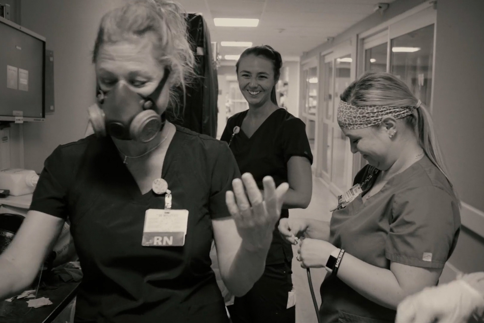 Black and white shot of nurse Kim Johnson in a safety respiratory mask joking with two colleagues, all in scrubs.
