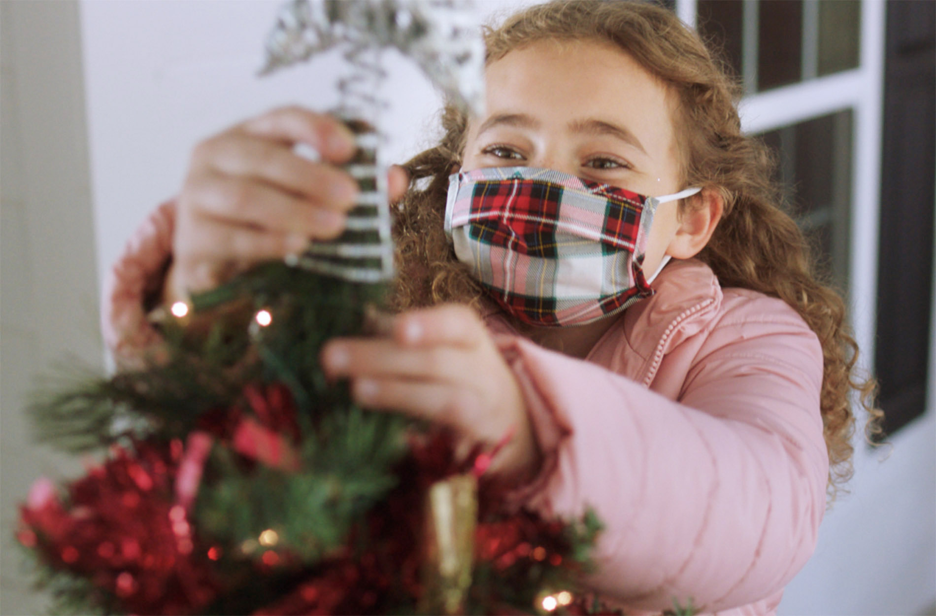 young girl in mask decorating for Christmas