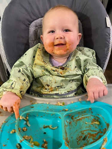 baby in high chair with food on face