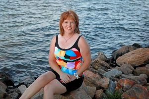 Karen Adkins, sitting on rocks by Lake Murray's shore in swimwear