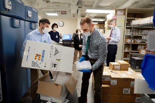 Pharmacist removing COVID vaccine from dry ice shipping box